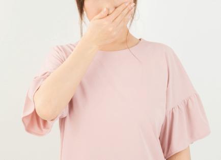 洗濯物の生乾きが臭くて鼻を押さえる女性の画像