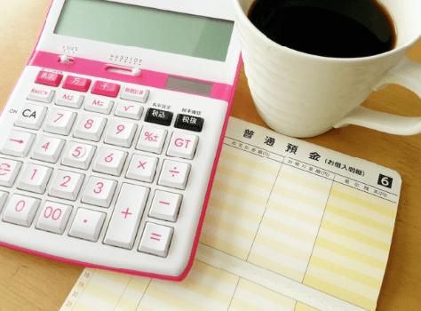 電卓と通帳とコーヒーの画像