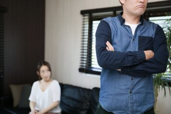 夫が怒っていて妻が反省している画像