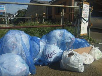 家庭ごみをブルーのネットのゴミ捨て場に捨ててある画像