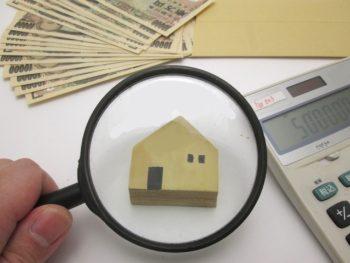 家の模型を虫眼鏡で見ている査定イメージ画像