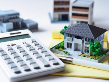 家の模型複数と電卓の査定イメージ