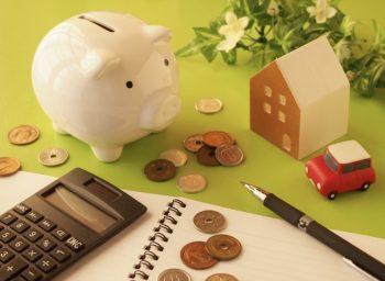 豚の貯金箱と家の模型と電卓の画像