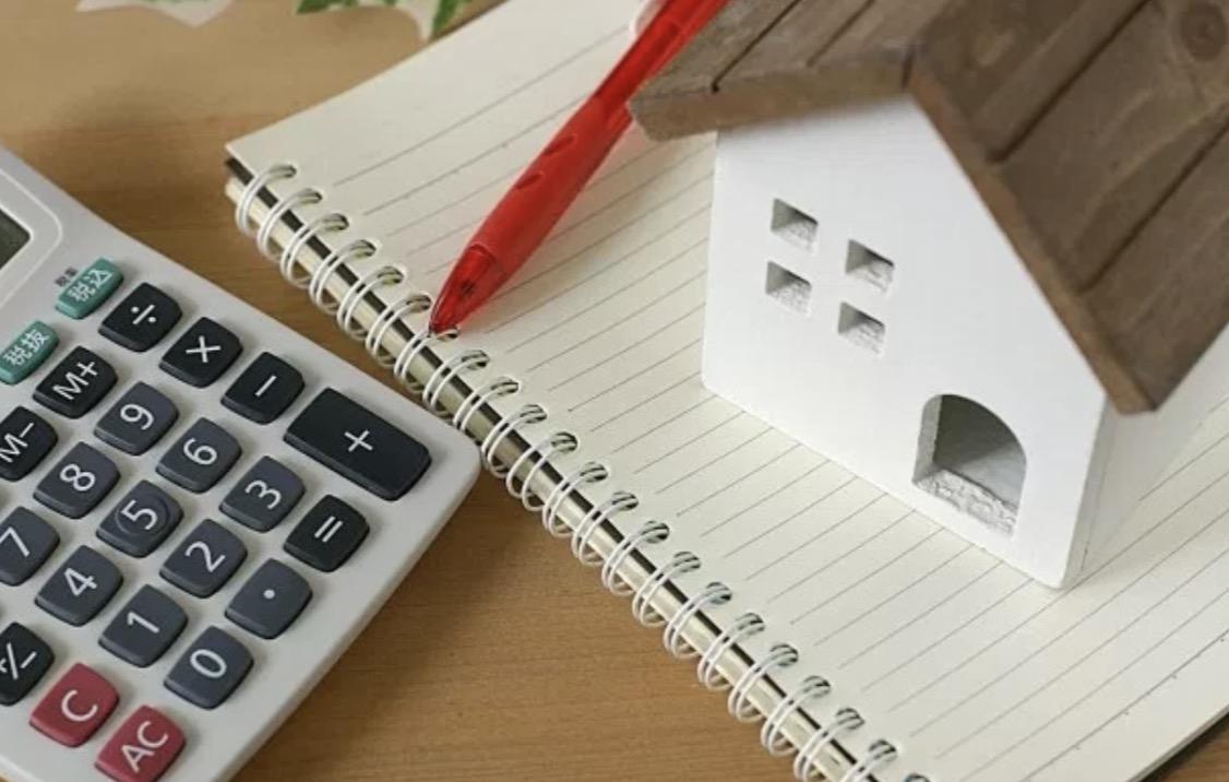 家の模型と電卓の画像