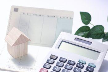 家の模型と貯金通帳と電卓の画像
