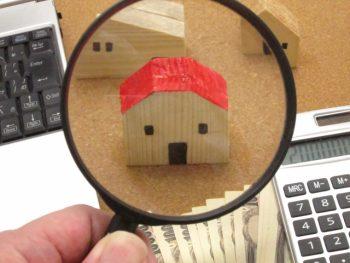 虫眼鏡で赤い屋根の家の模型を見る画像