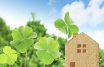 家の模型とクローバーの希望に満ちた画像